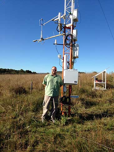Image of Dr Rosolem with the cosmic-ray soil moisture sensor installed at the the Federal University of Santa Maria SulFlux site in Brazil